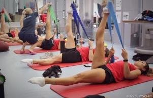Coach Natalia Didenko corrects one of her athletes as the team works on ballet leg stretches with elastics. Photo Christina Marmet/Inside Synchro.